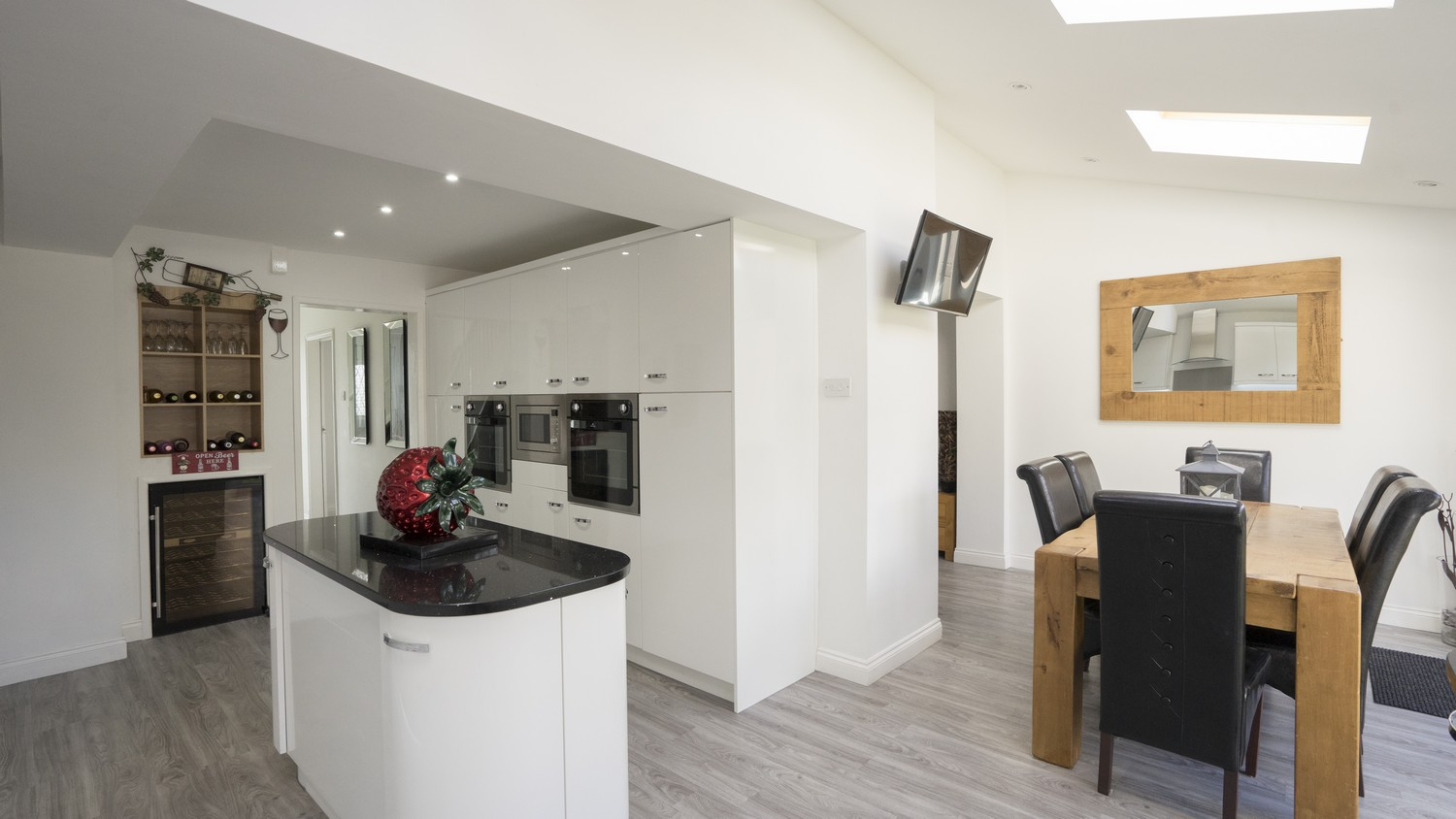 White gloss kitchen supplied with mirror black granite worktops as part of this open plan re-model.