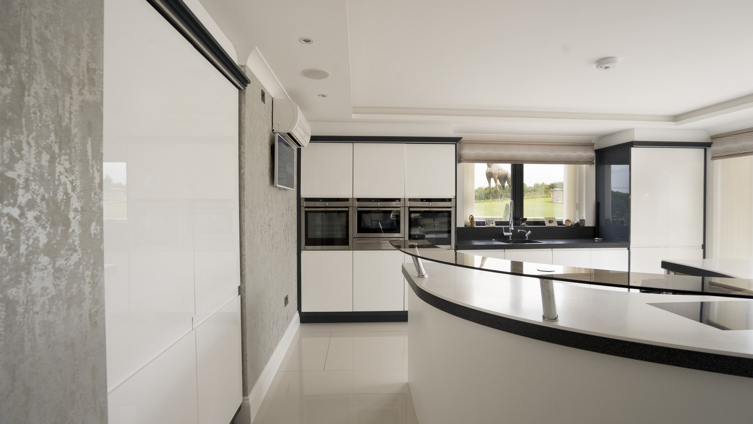 Straight on view of the gloss white Handle-less kitchen, dual larder cupboard houses a large fridge/freezer that has been located within the wall to give a feeling of space within the kitchen.