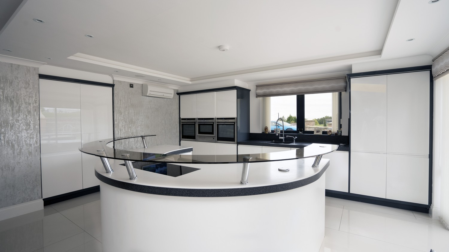 Gloss White Handle-less kitchen supplied and fitted in Aughton, Liverpool. This kitchen featuring a circular island at the center fo the kitchen a great space for both entertaining and dining.