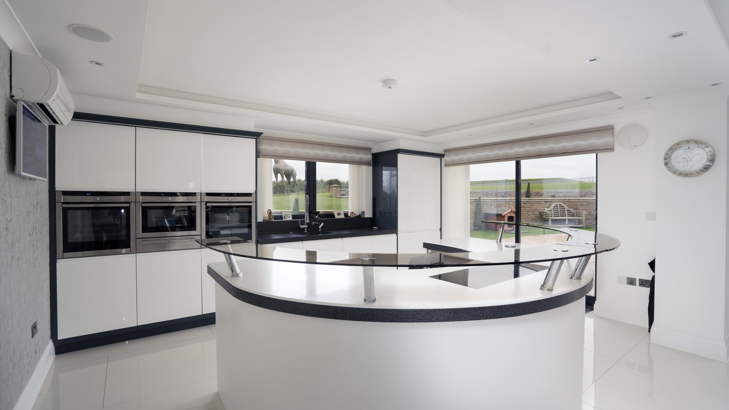 Gloss white kitchen with unique blue deep border and matching Corian worktops.