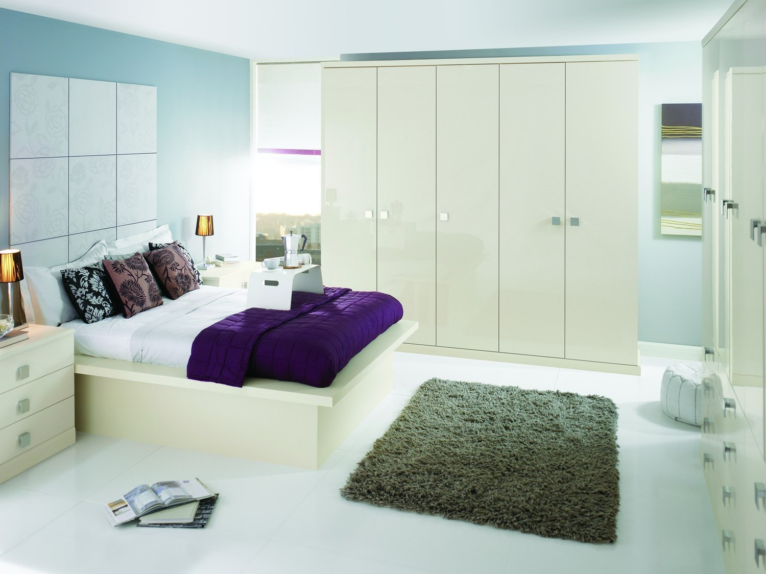 A modern gloss fitted bedroom furniture set finished in Oyster gloss with a modern square chrome handle. The bedroom set features a range of wardrobes and drawers, bed side cabinets and matching bed. This bedroom has added plenty of storage space to this medium sized bedroom, giving plenty of space for the home owners clothes and belongings.