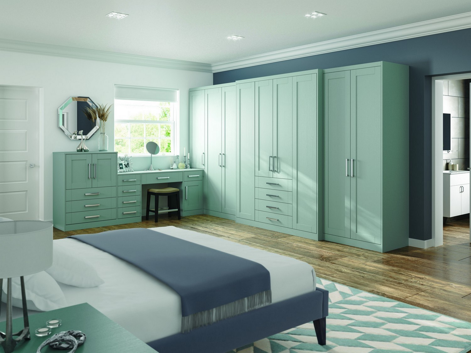 A green shaker bedroom furniture set designed for our client in St Helens featuring a simple chrome handle. This bedroom design feature various wardrobes, dressing table and bedside cabinets.