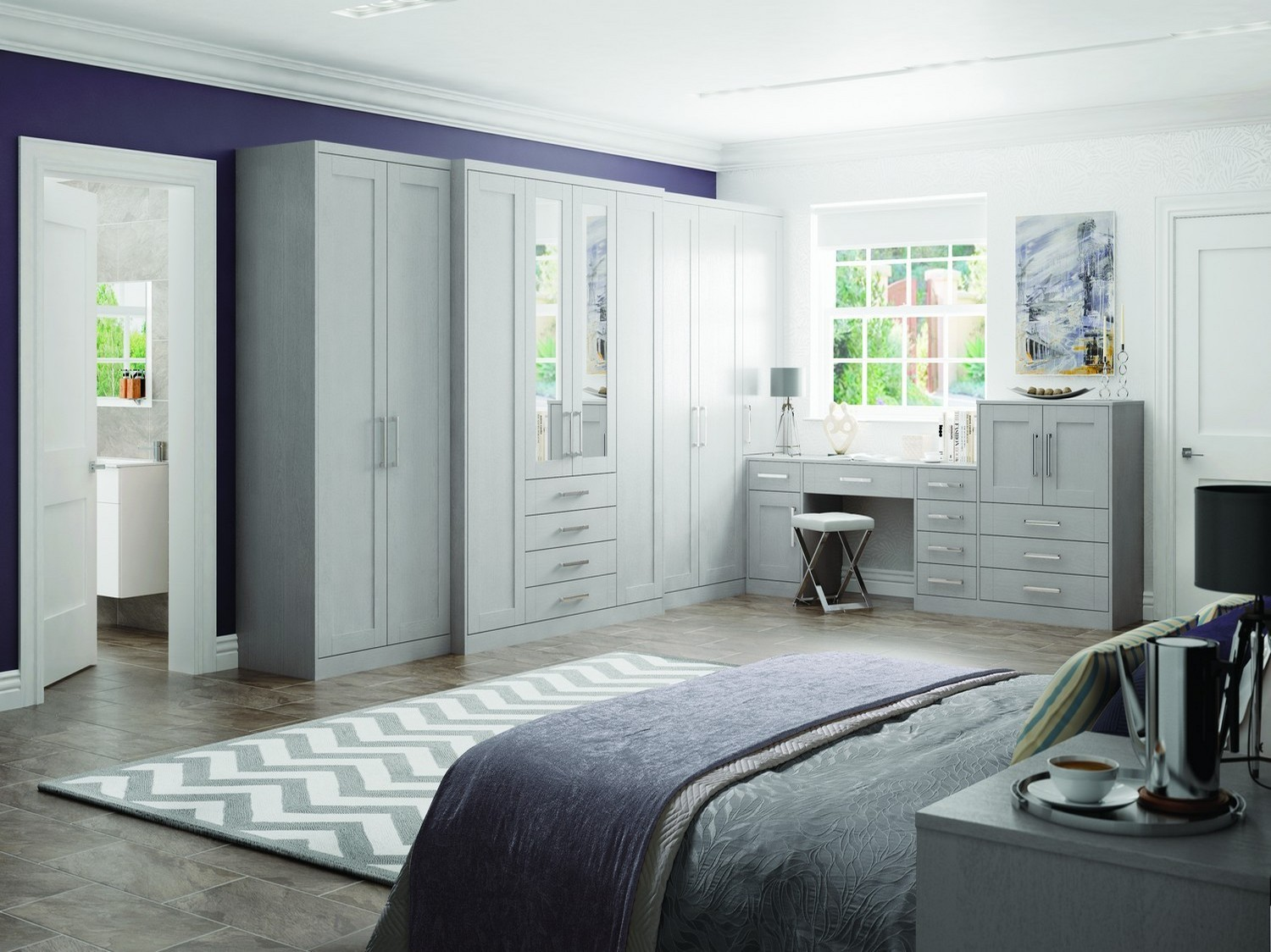 Larger built in bedroom furniture set finished in light grey with feature mirrors and mirror handles. The bedroom set features a range of wardrobes connected to a dressing table and storage draws. This bedroom furniture has been designed for a bedroom remodel in Maghull.
