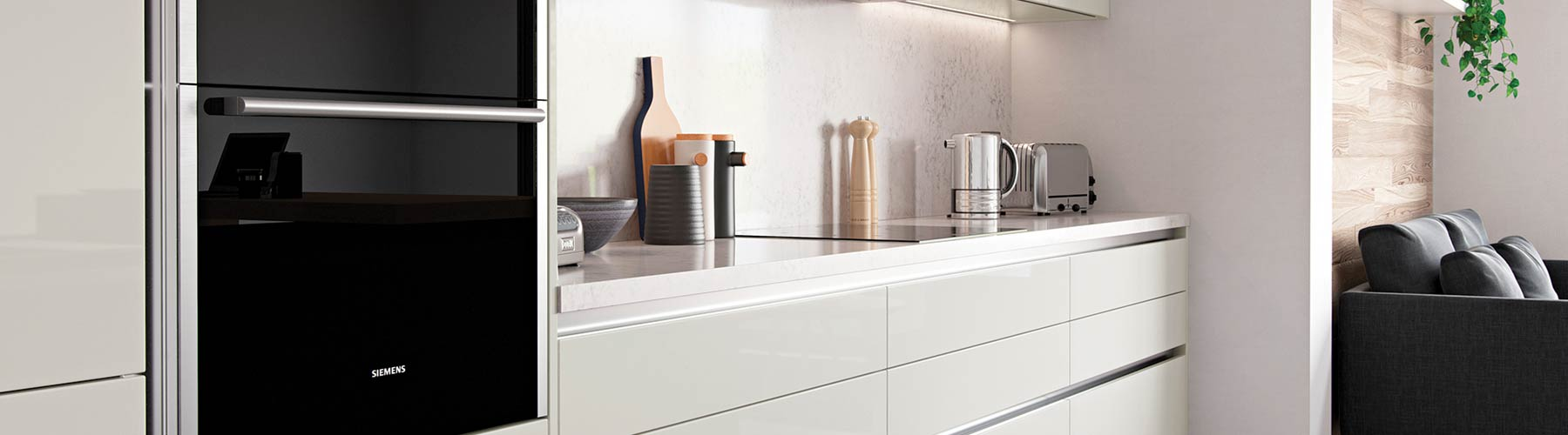 Gloss cream handle-less kitchen with white Corian worktop and integrated kitchen appliances.