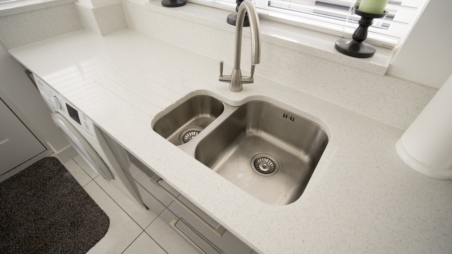 Stainless steel sink and tap, the sink has been under-mounted to the worktop which has been pre-cut in our Kirkby factory.