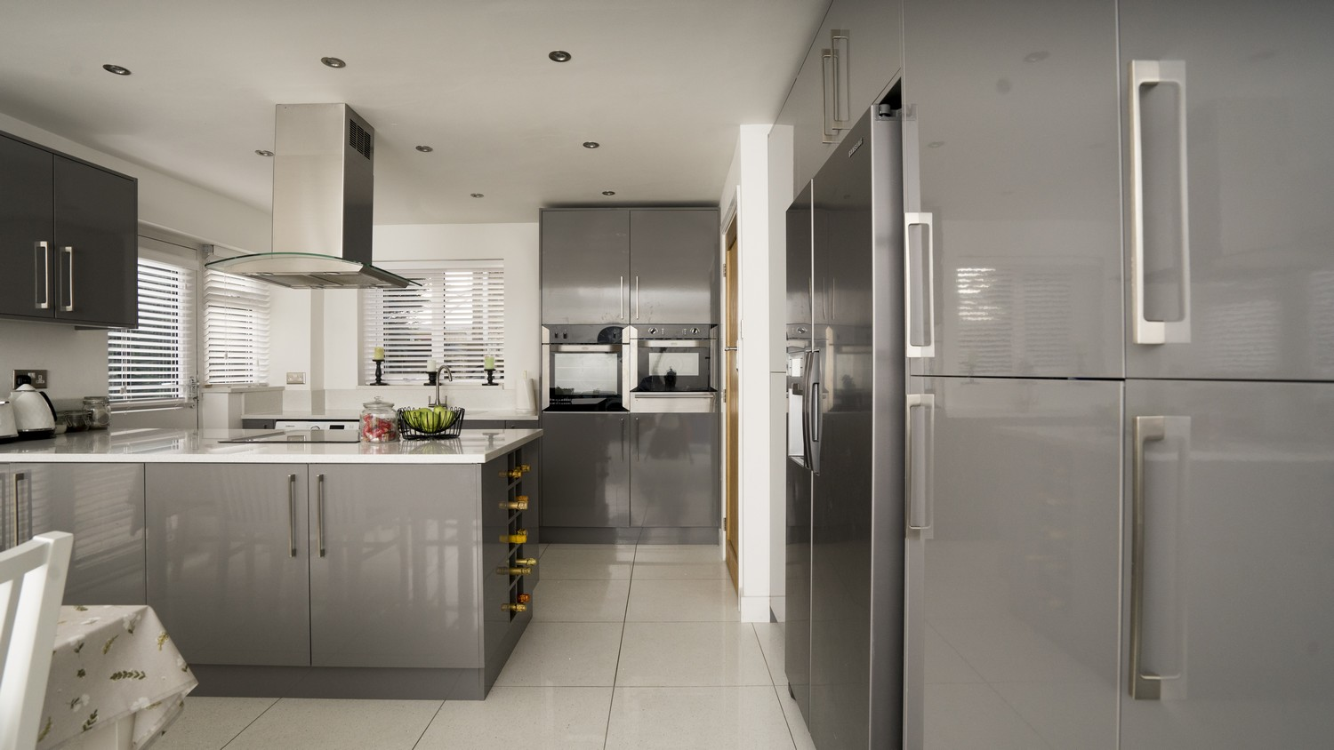 Grey gloss wine racks have also been installed in this family kitchen as shown at the end of the island.