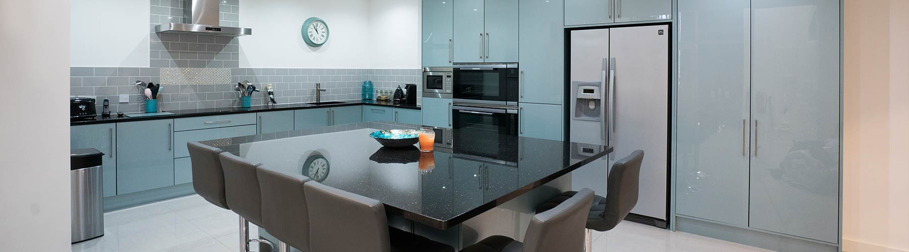 Large blue gloss kitchen with granite worktops and large island.