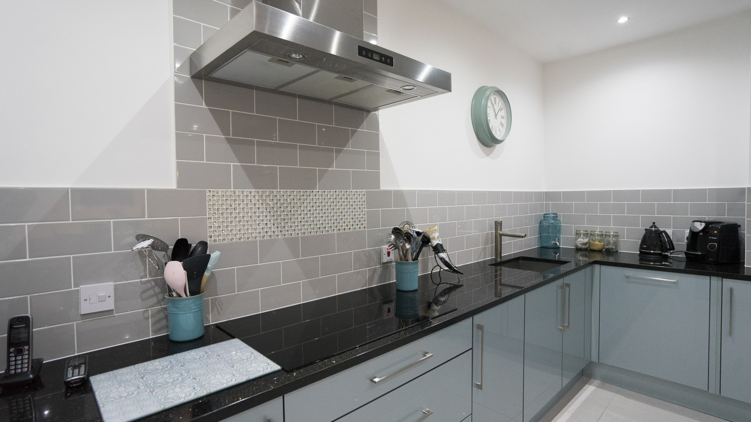 Blue gloss kitchen  with grey tiled splash back, large mirror finish black cooking hob and under-mount sink.