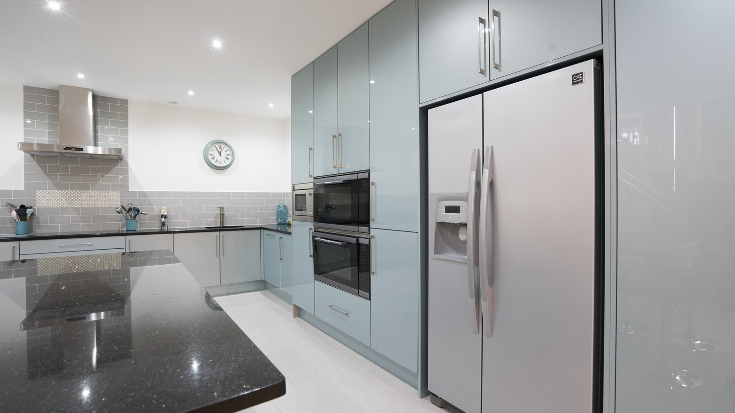Floor to ceiling feature larder units with integrated appliances and large fridge/freezer.