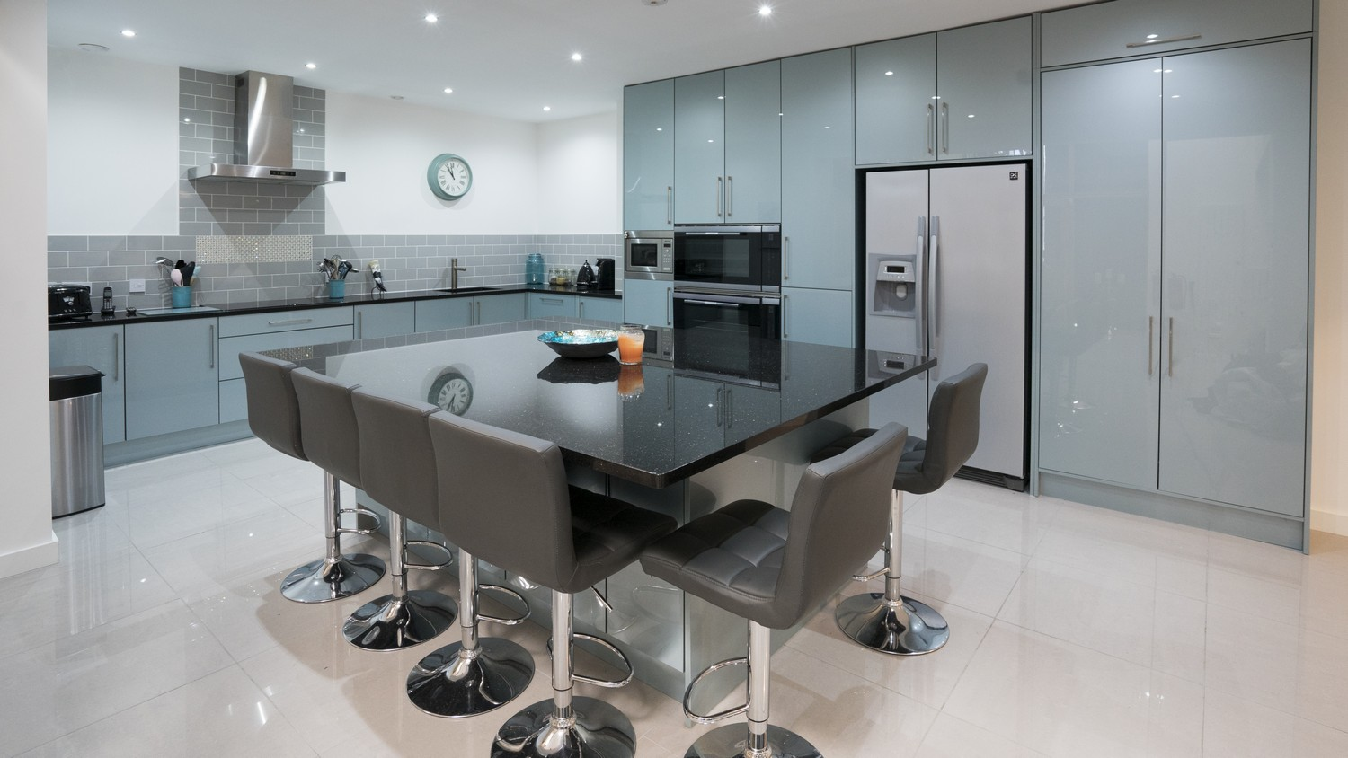 A large granite topped island with overhang and bar stools take center stage of this large high gloss kitchen.