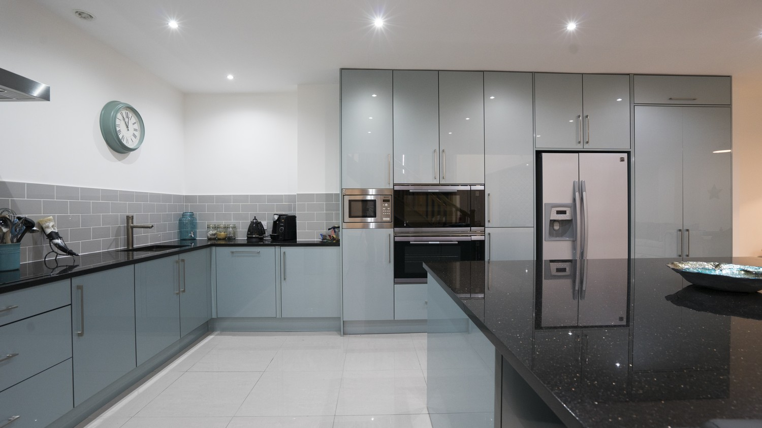 Straight on view of the large central island, lower cupboards and integrated appliances.