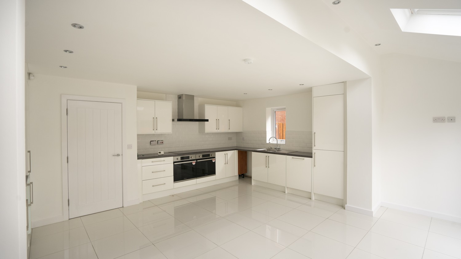 Gloss white kitchen installed featuring dual ovens, integrated appliances, lots of storage space and a large extractor fan.