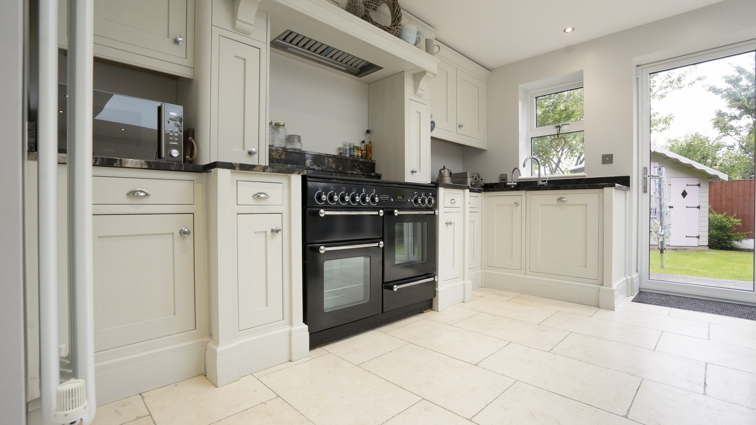Off White timber In-Frame kitchen cupboards with black granite worktops and feature timber mantel. Large double oven and gas hob for cooking, Installation Aintree, Liverpool.
