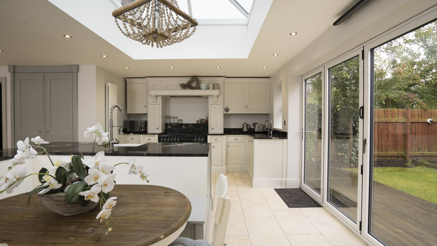 Full overview picture showing the timber In-Frame kitchen flooded with light from the roof lantern above.