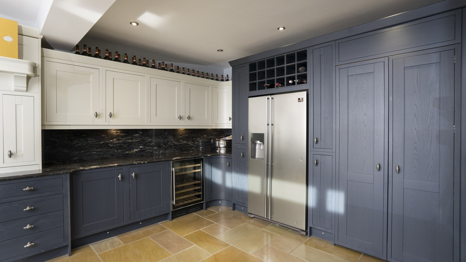 Timber inframe kitchen showing fridge/freezer and tall larder style cupboards. All units have been finished with a painted finish in midnight blue and Ivory.