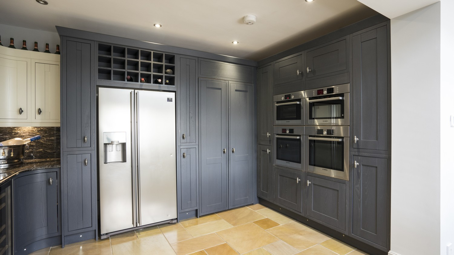 Close up of the larder cupboard housing the various built in appliances, wine rack and hidden entry to the utility room.