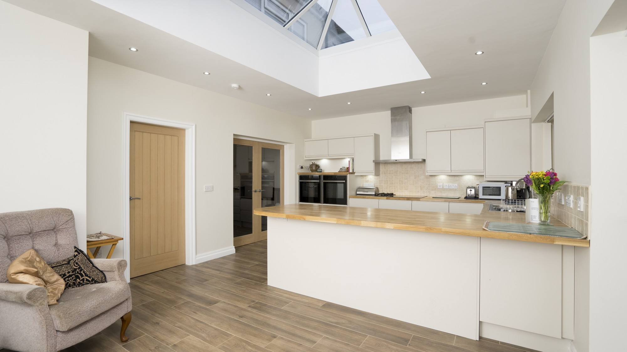 Overview of handleless kitchen in Wavertree, Liverpool featuring gloss cream doors and oak block worktops.