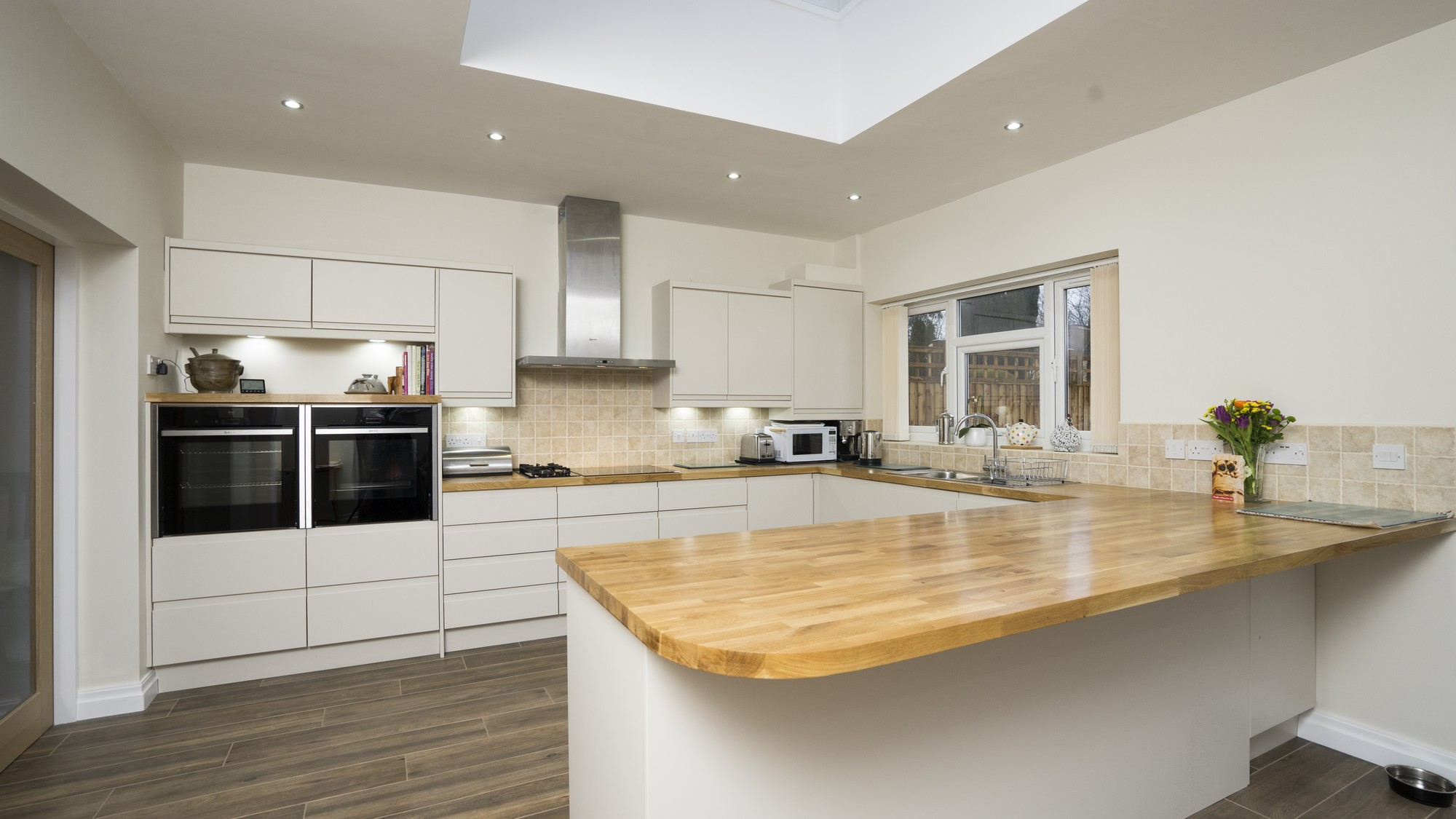 Close up of the large breakfast island with oak worktop and plenty of seating space.
