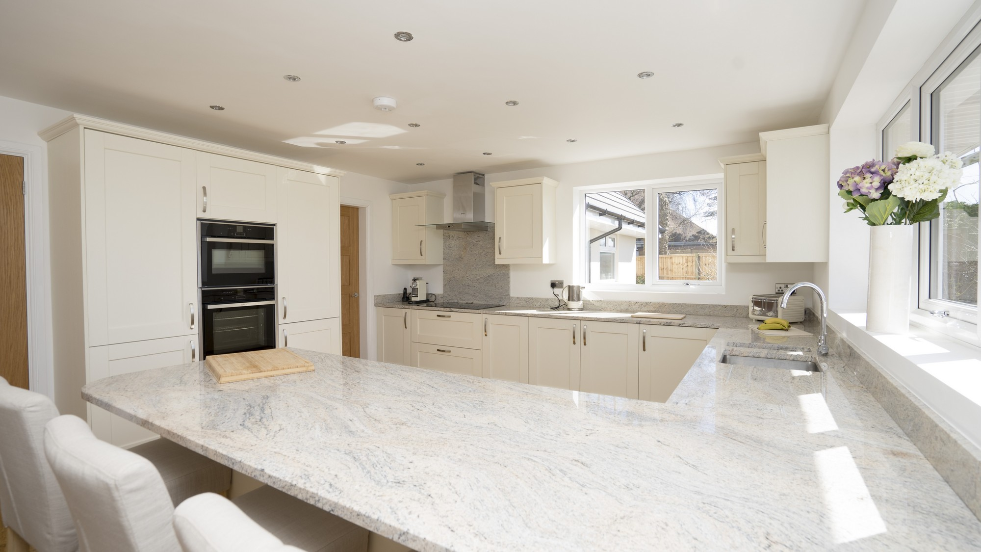 Large Ivory shaker kitchen with stainless steel handles and granite worktops. The granite has been cantilevered over the kitchen cupboards to create an island style dining area.