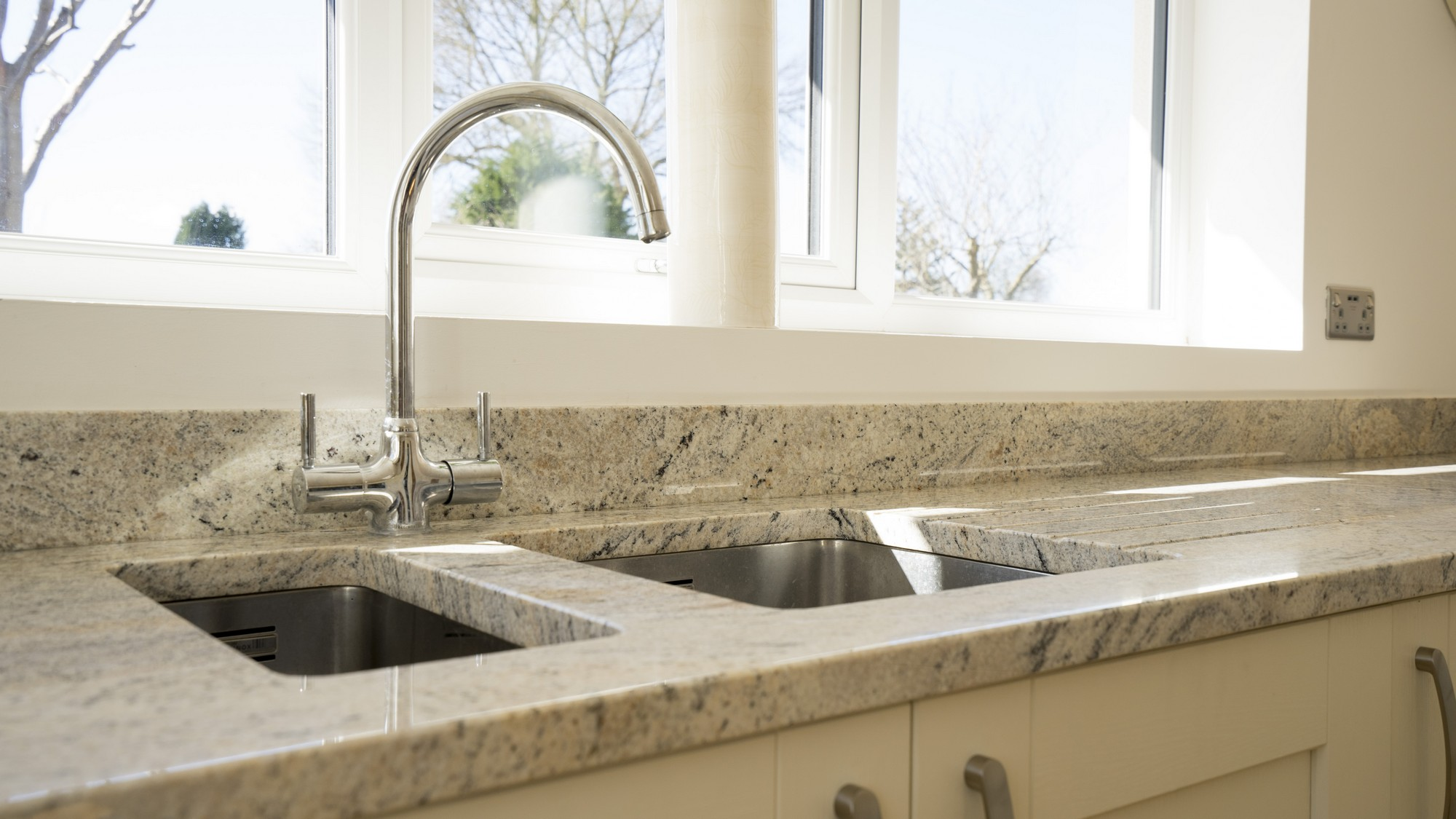 Close up of the stainless steel sink and tap, under-mounted to the granite worktops.
