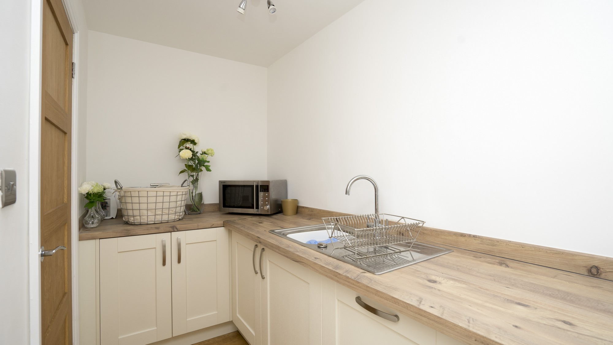 Image of the utility room fitted out with matching cabinets and composite worktops.