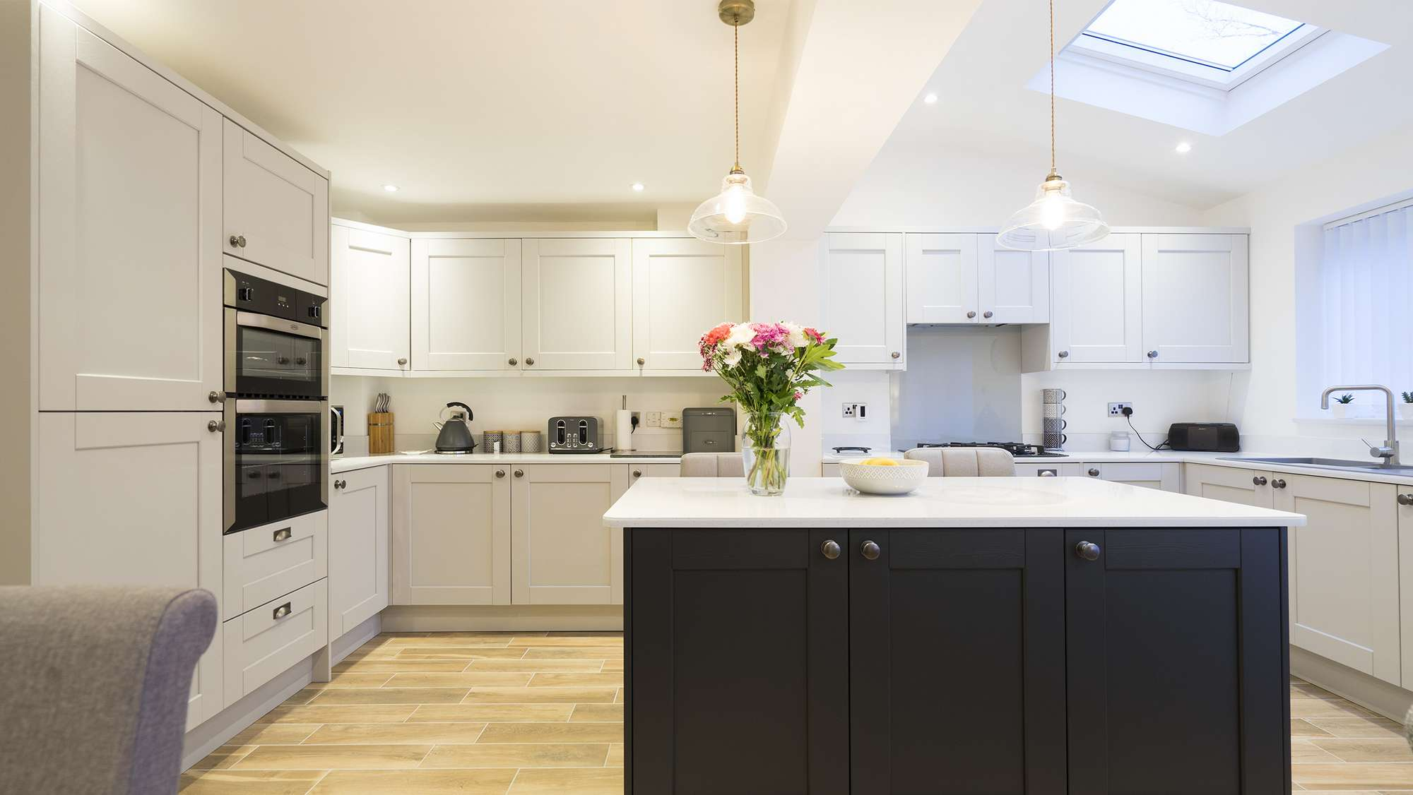 Straight on view of this two tone shaker kitchen, featuring traditional handles and drawer pulls.
