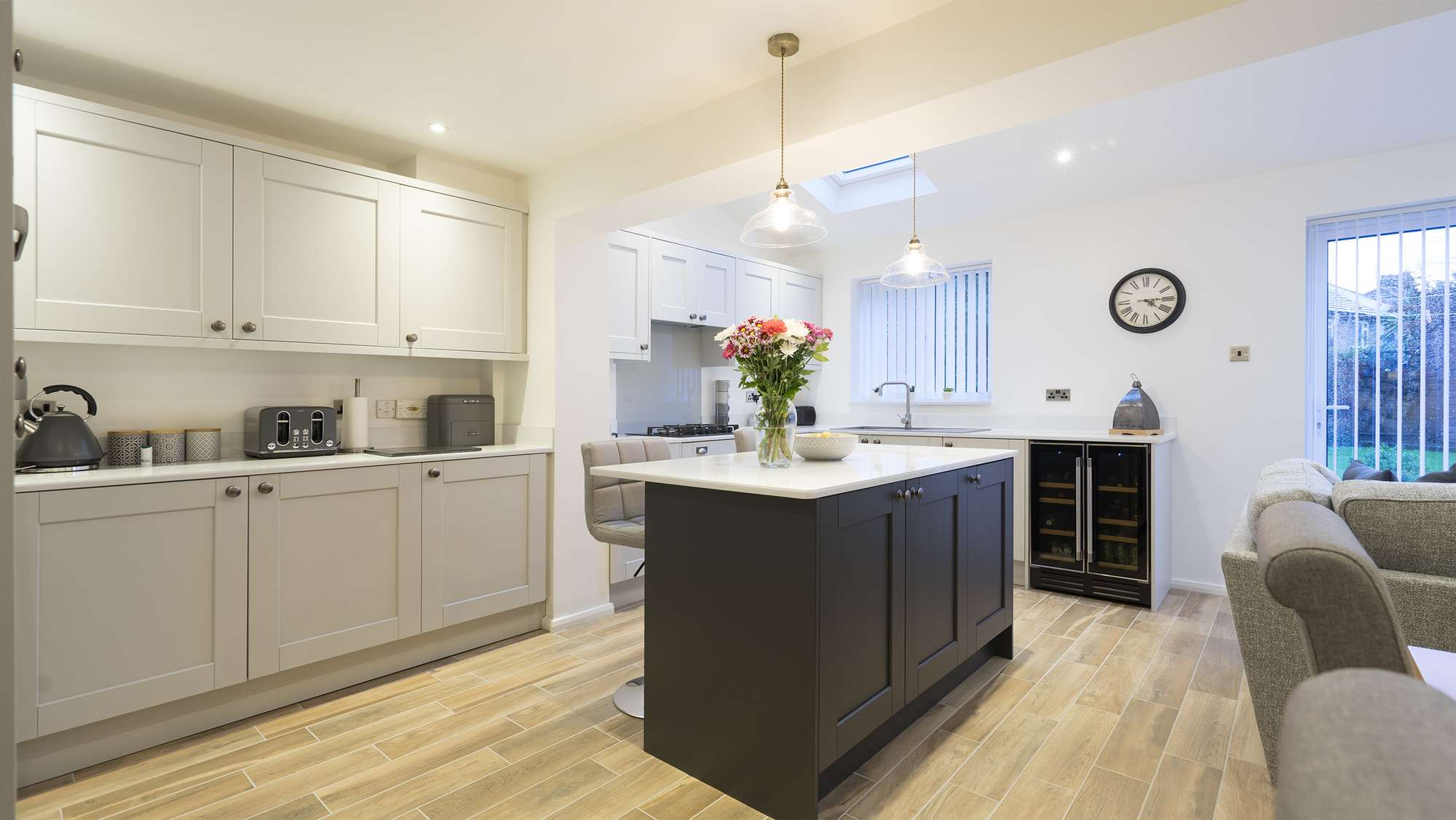 Light grey shaker kitchen with dark grey contrasting island and seating area.