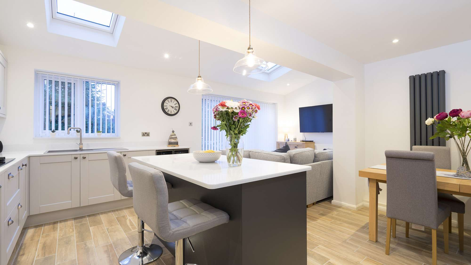 Overview of the open plan living space featuring a shaker kitchen and Corian worktops.