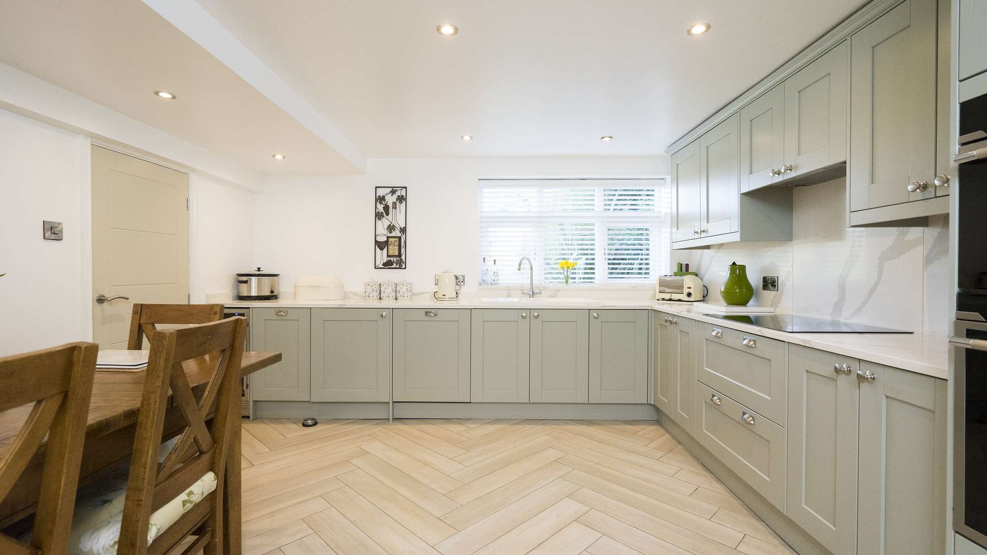 Straight on view of this large shaker kitchen in olive green with white marble style worktops and matching backsplashes.