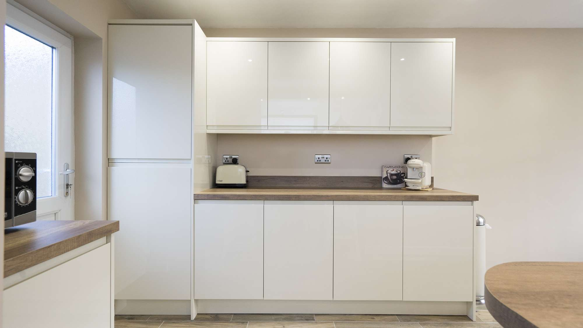 Straight on shot of the handleless kitchen cabinets.,
