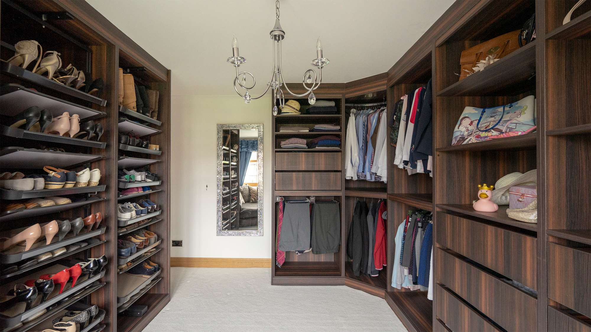 Image showing most of the walk-in wardrobe with the rotating shoe racks on the left side and clothes storage on the right.